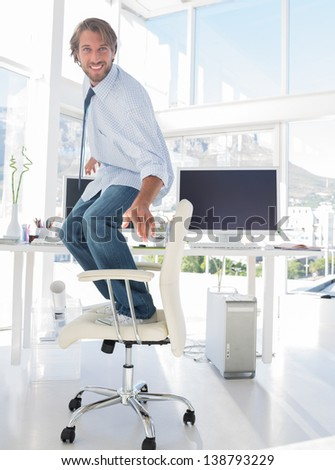 Man surfing his swivel chair in bright modern office