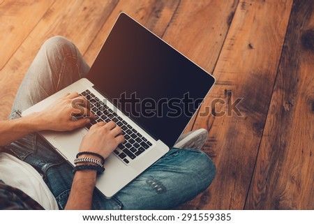 Man surfing the net. Top view of man working on laptop while sitting on the wooden floor - stock photo