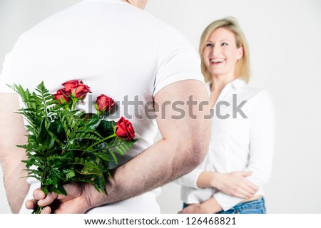 Man surprise his girlfriend with red roses - stock photo