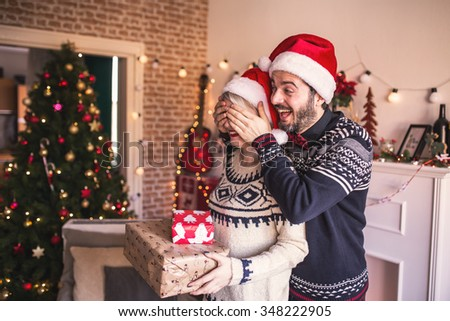Man surprising his girlfriend with a Christmas gift. - stock photo