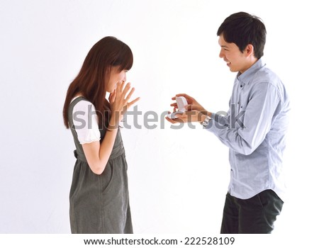 Man surprising his girlfriend with a proposal in house. - stock photo