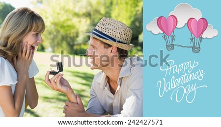 Man surprising his girlfriend with a proposal in the park against cute valentines message - stock photo