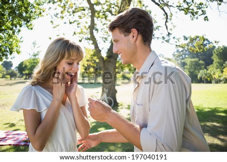 Man surprising his girlfriend with a proposal in the park on a sunny day - stock photo
