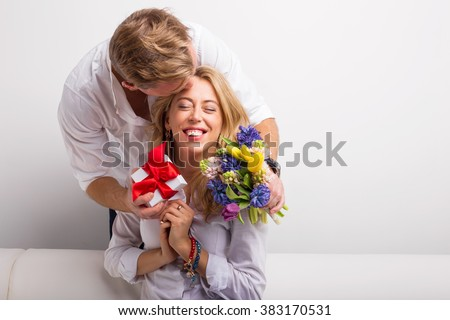 Man surprising his woman with flowers and kiss on the cheek  - stock photo