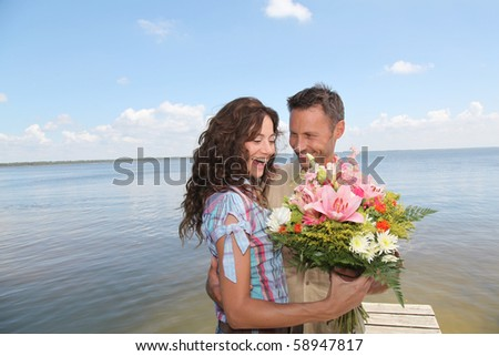 Man surprising woman with bunch of flowers - stock photo