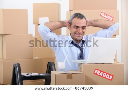 Man surrounded by cardboard boxes using his laptop - stock photo