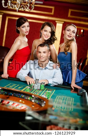 Man surrounded by girls gambles roulette at the casino - stock photo