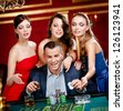 Man surrounded by women plays roulette at the gambling house - stock photo