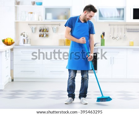 Man sweeping floor in the kitchen - stock photo