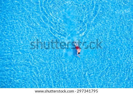 Man swim in the pool at the hotel. View from above.  - stock photo