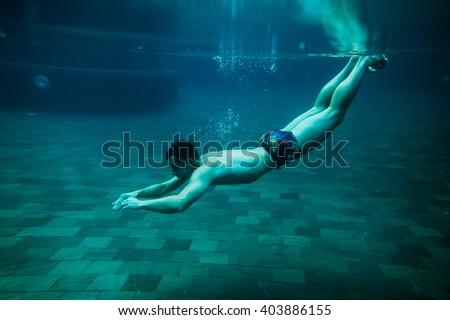man swim underwater pool on vacation leisure time - stock photo