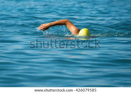 Man swimmer swimming crawl in blue sea.Training for triathlon - stock photo