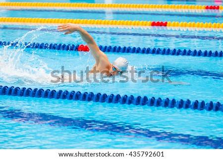 Man swimmer swimming crawl in blue water. - stock photo