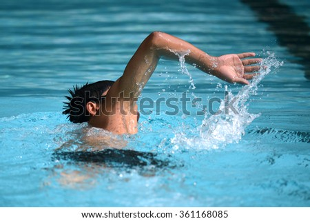 Man swimmer swimming on pool with freestyle stroke for race
