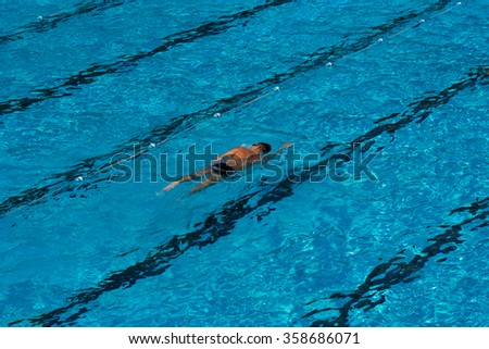man swimming in a blue swimming pool - stock photo
