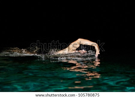 Man swimming in a swimming pool at night, training crawl style. - stock photo