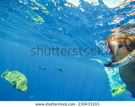Man swimming under water on a background of beautiful marine fish