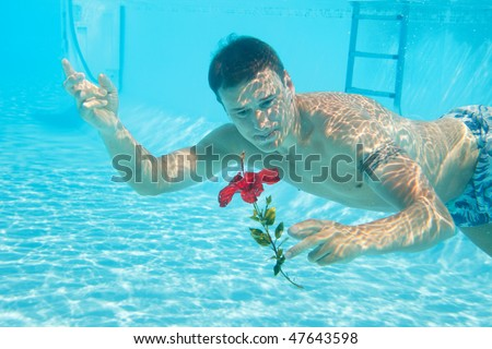 Man swimming with open eyes underwater in pool holding flower - stock photo