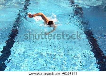 man swims in swimming pool - stock photo