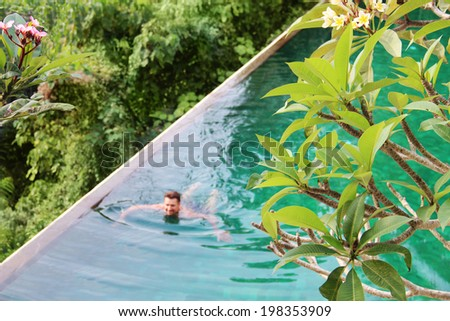 man swims in the pool top view - stock photo
