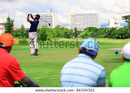 man swing golf club with friend, in golf course. - stock photo