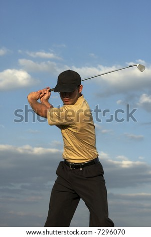 Man swinging a golf club late after noon - stock photo