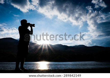 Man take a photograph during sunset silhouette - stock photo