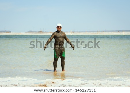 man takes a mud bath in the salty lake Baskunchak - stock photo