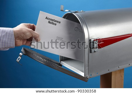 Man takes Acceptance Notice out of an open mailbox - stock photo