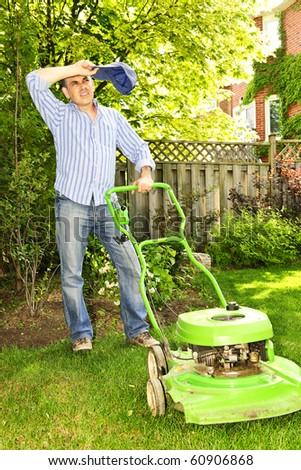 Man taking a break while mowing lawn on hot summer day - stock photo