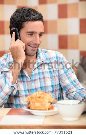 Man taking a call at breakfast - stock photo