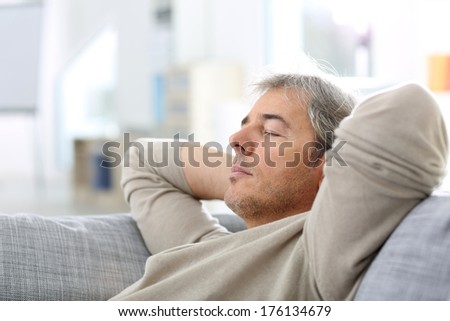 Man taking a nap in sofa at thome - stock photo