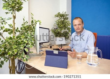 Man, taking a phone call in a paperless office, using various electronics, working in the cloud in an environmental friendly way - stock photo