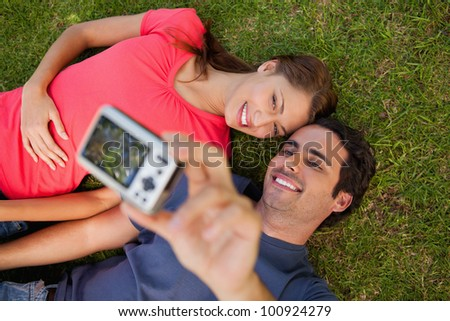 Man taking a photo of him with his friend while lying side by side on the grass - stock photo