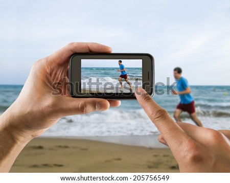 man taking a picture with your mobile phone a one man running for joy on the beach - stock photo