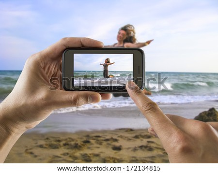 man taking a picture with your mobile phone a one woman jumping for joy on the beach - stock photo