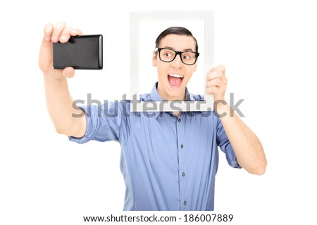 Man taking a selfie and holding a picture frame isolated on white background - stock photo