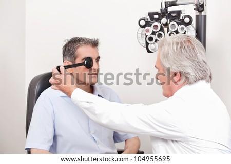 Man taking an eyesight test examination - stock photo