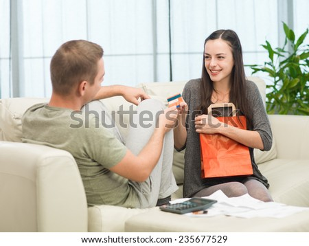 man taking credit card away from his girlfriend after she went shopping - stock photo