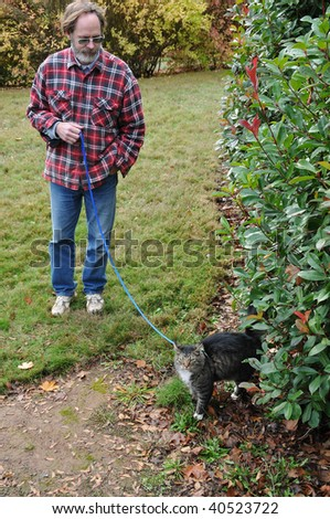 Man taking his cat for a walk in his lawn