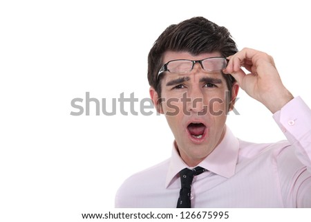 Man taking his glasses off in dismay - stock photo