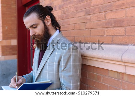Man taking notes on his Notebook