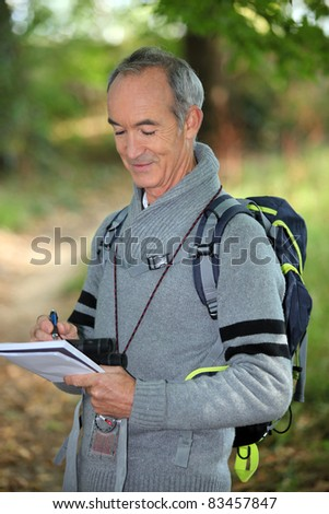 Man taking notes outside