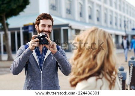 Man taking photo of girlfriend on holiday - stock photo