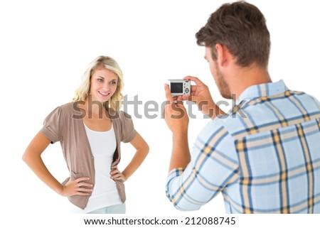 Man taking photo of his pretty girlfriend on white background - stock photo