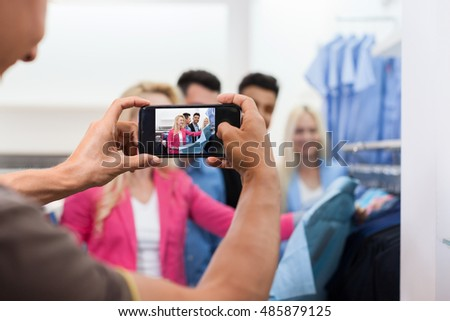 Man Taking Photo Of Young People Shopping, Happy Smiling Friends Two Couple Customers In Fashion Shop Choosing Clothes Shirts