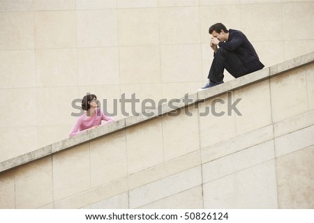 Man taking photograph of woman on stairway