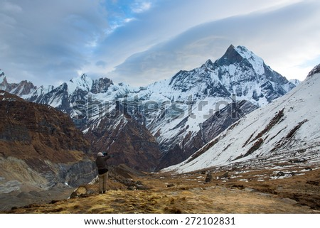 Man taking photos of Machhapuchchhre (Fish Tale) from Annapurna Base Camp Himalaya Mountains in Nepal - stock photo