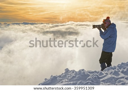 Man taking photos on top of Kasprowy Wierch in Zakopane in winter. Zakopane is a town in Poland in Tatra Mountains. Kasprowy Wierch is a mountain in Zakopane and is the most popular ski area in Poland