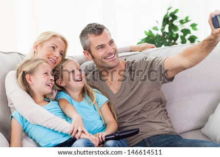 Man taking picture of his children and wife sitting on a couch - stock photo